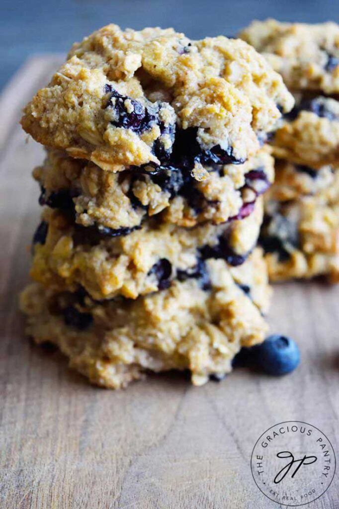 A stack of four cookies from this blueberry breakfast cookies recipe on a cutting board. You can see blueberries throughout the cookies.