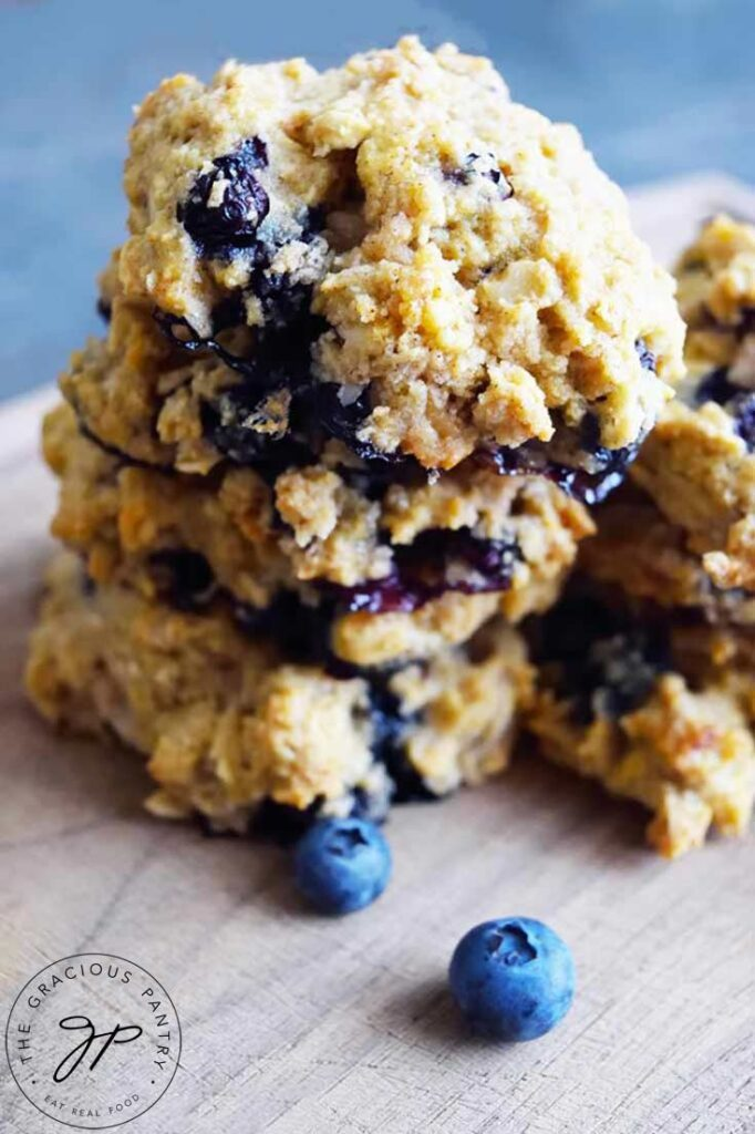Two stacks of breakfast cookies on a cutting board with fresh blueberries scattered around the cookies. This breakfast cookies recipe comes together fast and easy! Give it a try!