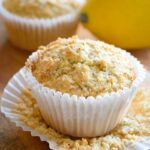 A Gluten Free Lemon Poppy Seed Muffin sits on an unfolded cupcake paper with a lemon behind it.