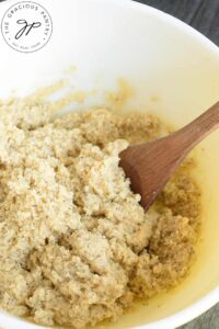 Gluten Free Lemon Poppy Seed Muffins dough in a mixing bowl with a wooden spoon.