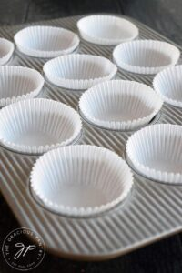 A muffin pan lined with cupcake papers, ready to make these Gluten Free Lemon Poppy Seed Muffins.