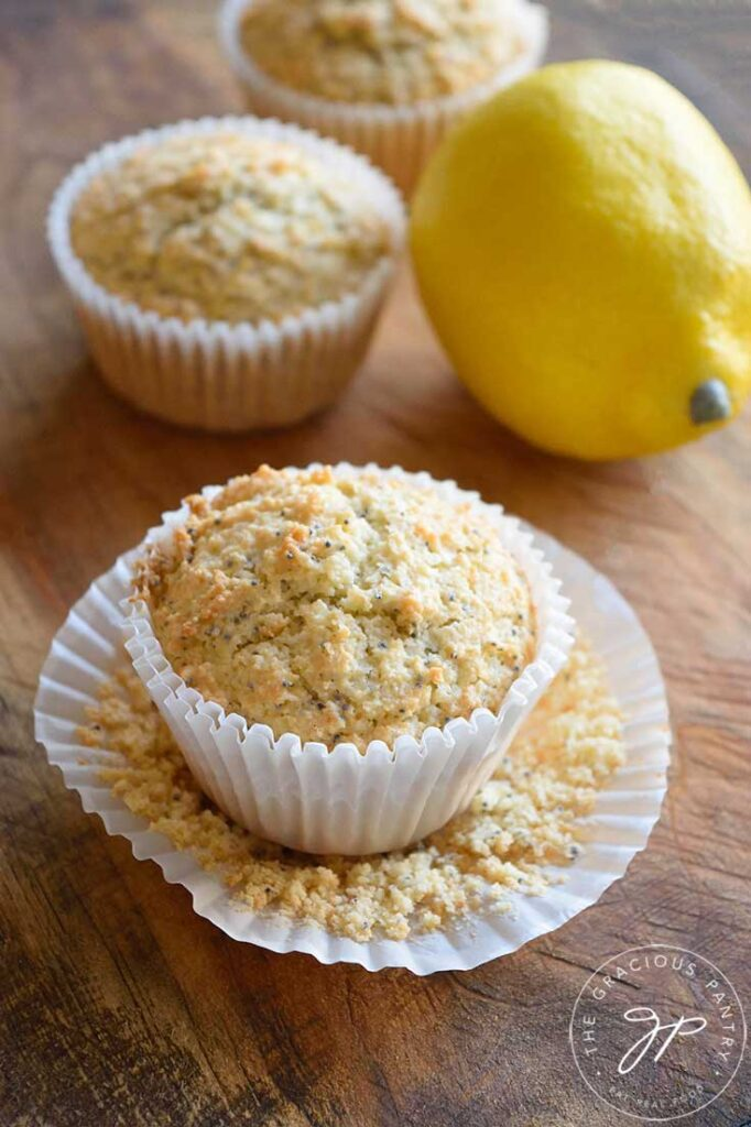 Single Gluten Free Lemon Poppy Seed Muffins on a cutting board with a whole lemon next to them.