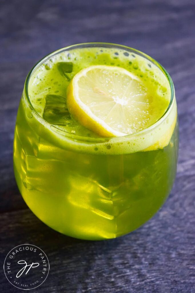 Green Lemonade in a stemless wine glass with a lemon slice resting on the ice.