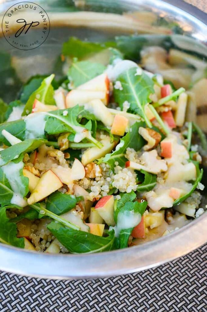 A side view of this Kale Quinoa Salad in a mixing bowl with dressing on it.