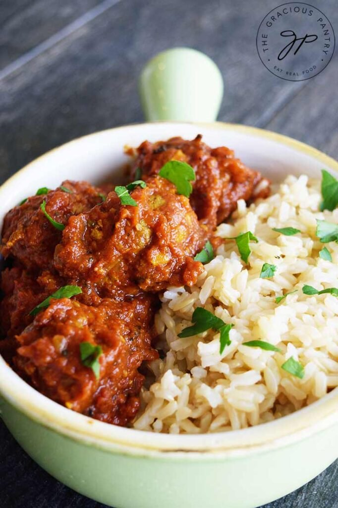 Kofta Curry Recipe in a light green crock, served with a side of brown rice.
