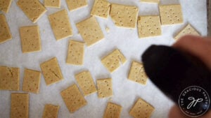 Spritzing the raw oat crackers with a light coat of oil just before they go into the oven.