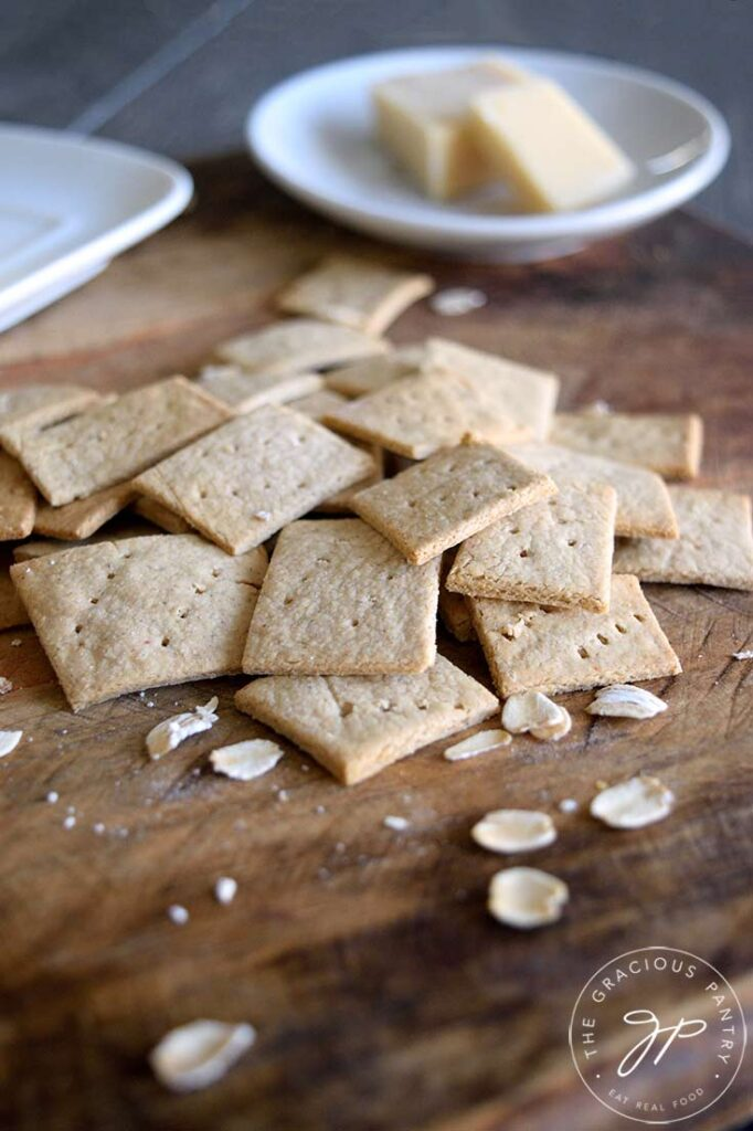 And up close view of the oat crackers on a cutting board. A few whole oats are scattered around them.