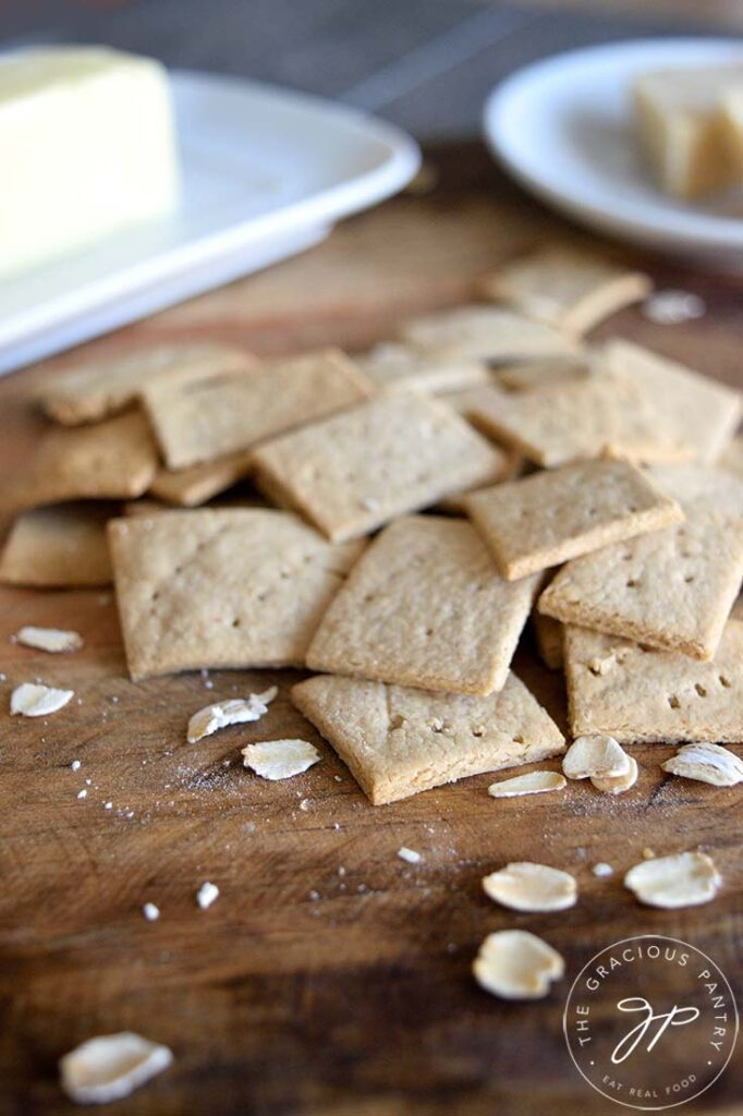 A pile of oat crackers sit with a butter dish just behind them on the counter.