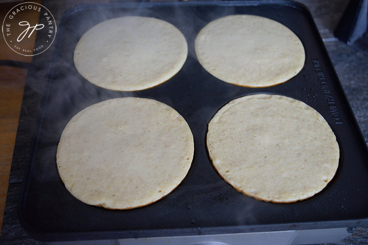 Pancakes cooking on a griddle.