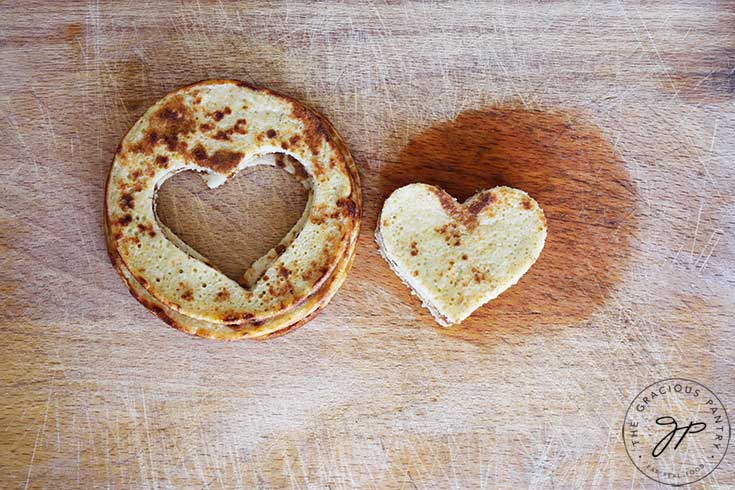 Two piles of pancakes sit next to each other on a cutting board. On the left are the regular pancakes with hearts cut out of the center. On the right are the cut out hearts for a Valentine Pancake Sandwich.
