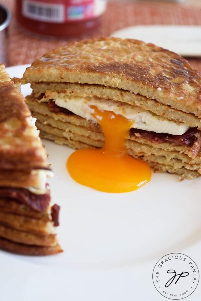 A pancake sandwich sits cut in half. The egg yolk in the center is drizzling down to the center of the plate.