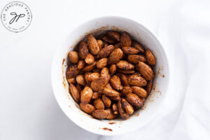 Mixing the almonds and spices together with the oil in a small, white mixing bowl.