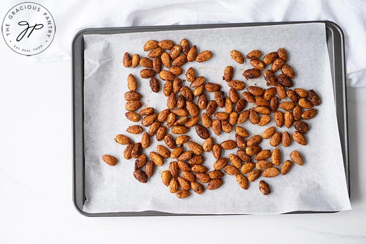 The prepared almonds spread out on a baking sheet, lined with parchment paper.