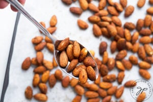 The finished, roasted almonds, just out of the oven. A spoon holds a few of them close to the camera.
