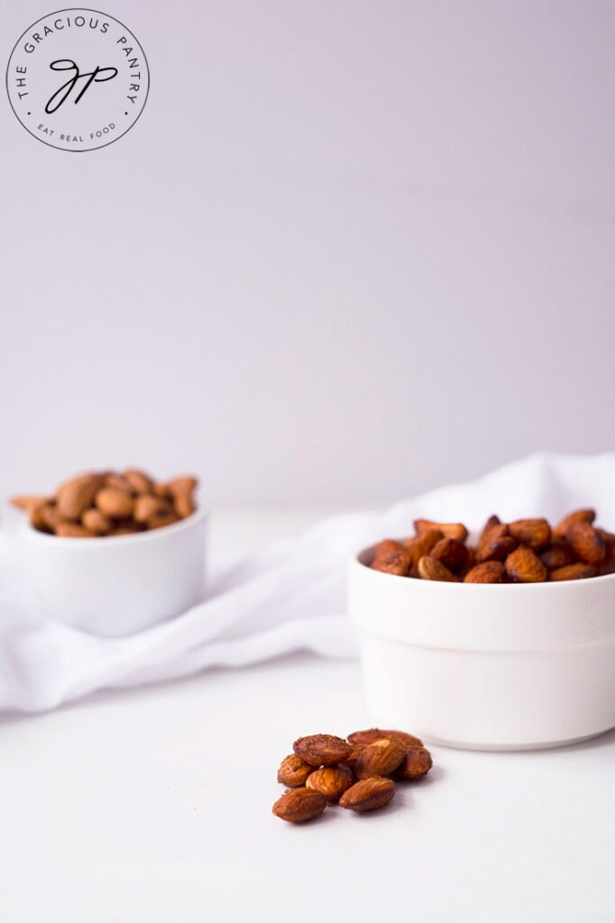A side view of two small, white bowl sitting on a white background, filled with Spicy Roasted Almonds.