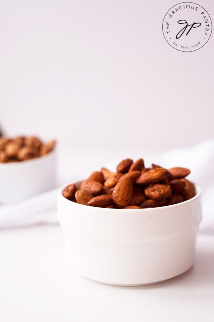An up close side view of a small white bowl filled with Spicy Roasted Almonds.
