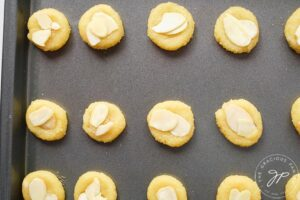 Almond cookies lined up on a cookie sheet, ready to go into the oven for baking.