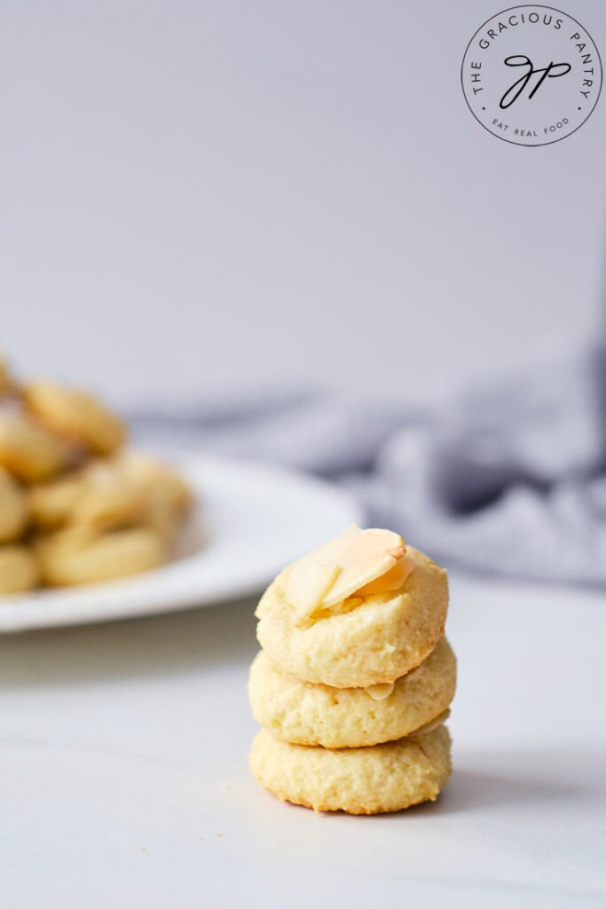 A stack of three Almond Cookies sitting in front of plate filled with more cookies.