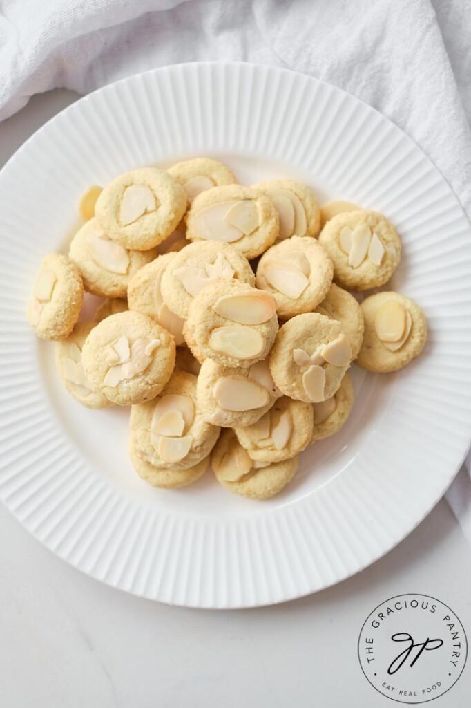 An overhead view looking down onto a white plate filled with these Almond Cookies.