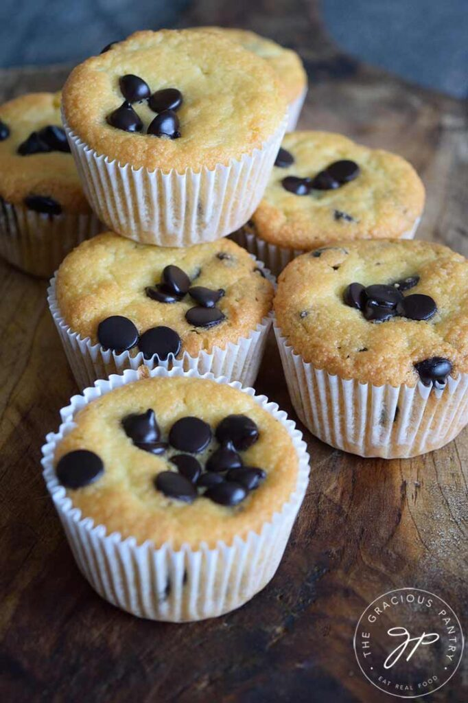 A stack of almond flour muffins sitting on a wooden surface. Chocolate chips are baked into the tops of the muffins.
