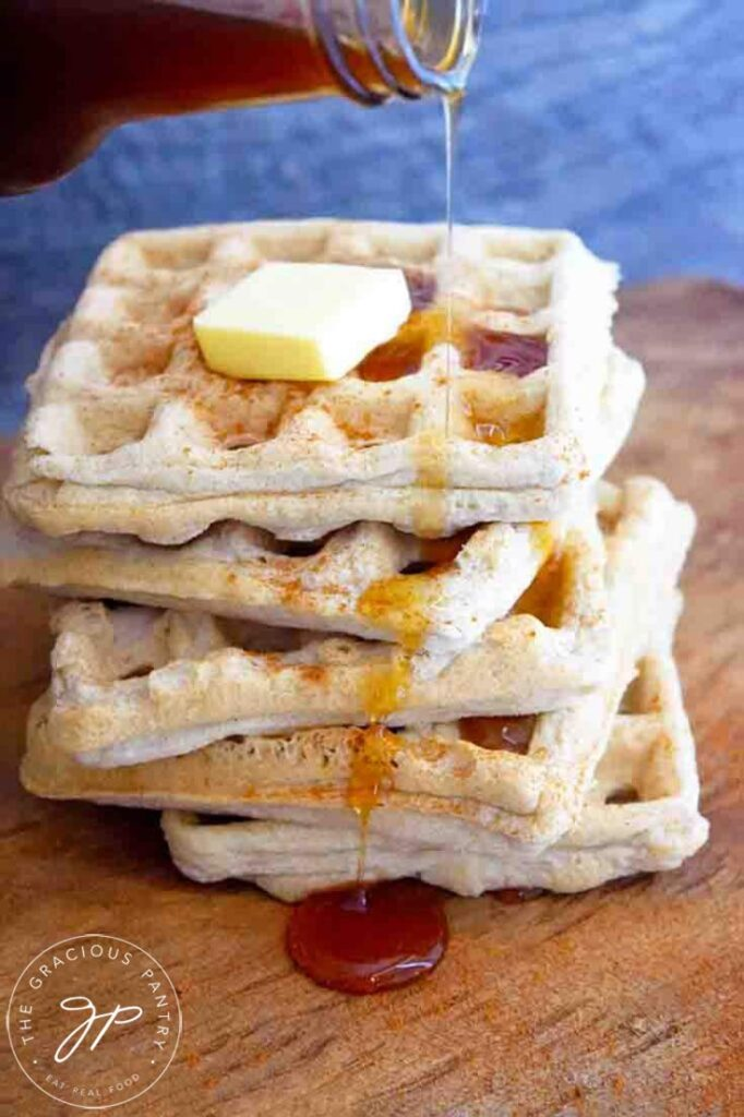 A stack of Almond Flour Waffles with a pat of butter on top and some maple syrup being poured over the top.