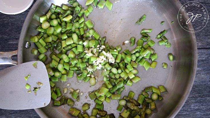 Adding garlic to the skillet.