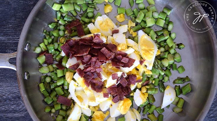 Adding in the bacon bits to this Asparagus Salad Recipe