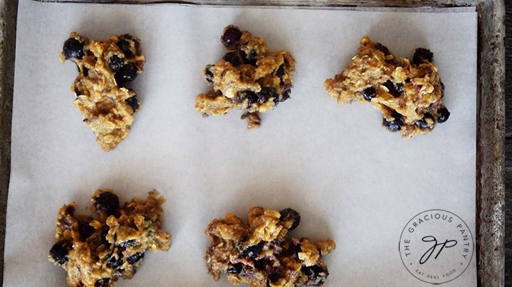 The cookie batter spooned onto a parchment lined cookie sheet.