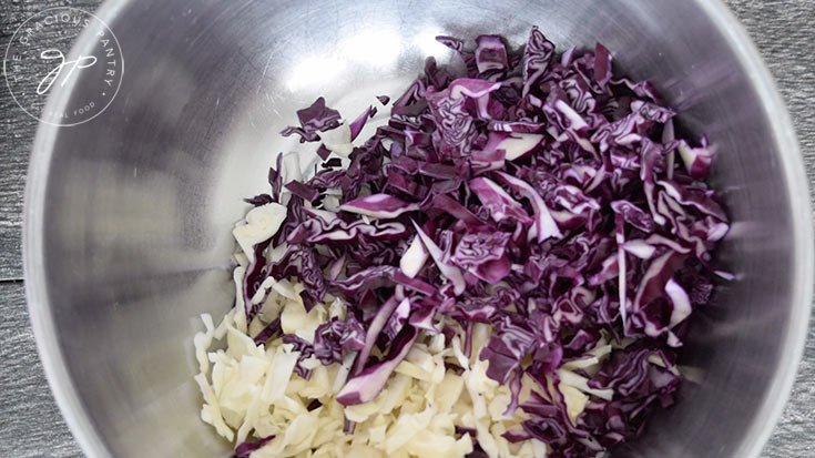 The green and purple cabbage, cut and ready to mix in a mixing bowl.