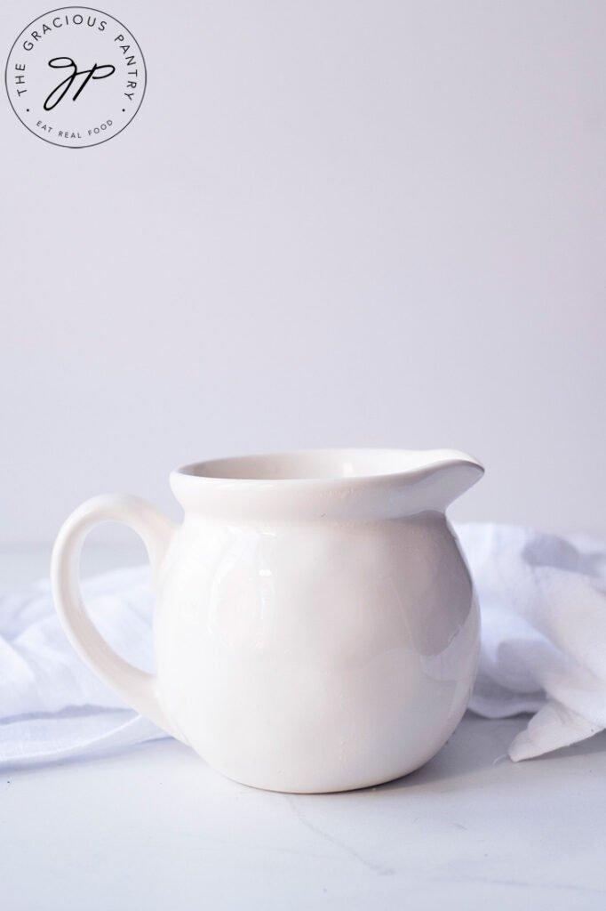 A white pitcher sits on a white background, ready to be filled with the finished Chicken Broth Gravy Recipe.