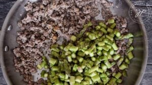 Adding the asparagus to the skillet for this Ground Turkey Skillet Dinner Recipe.