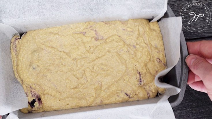 Tapping the loaf pan on the counter top to settle the batter in the pan.