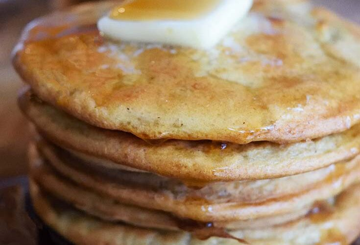 A stack of Leftover Oatmeal Pancakes with a pat of butter on top and maple syrup drizzled over the top.