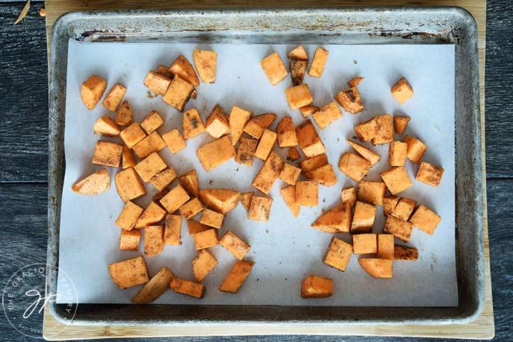 The chopped and seasoned sheet potatoes on a baking pan.