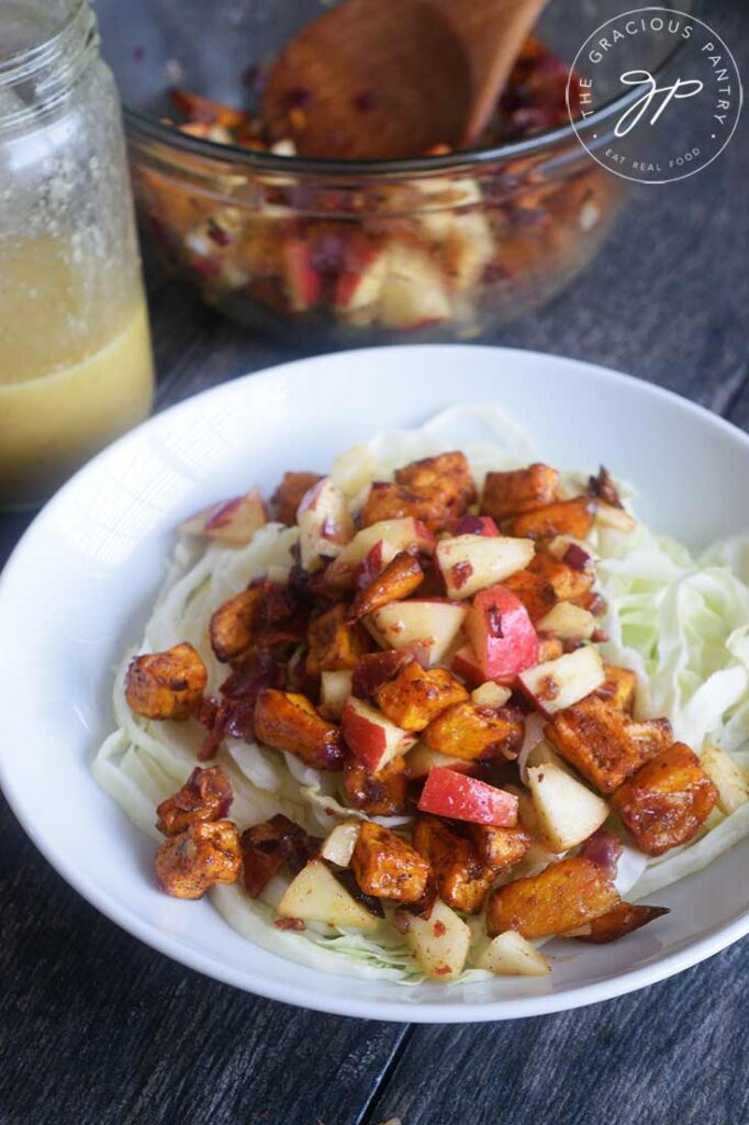 A front view of this Roasted Potato Salad on a table with dressing and a second bowl sitting behind it.