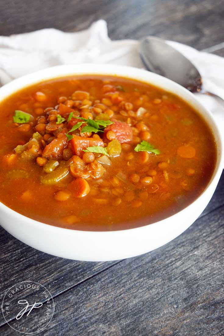 A front view of a white bowl filled with this Slow Cooker Curry Lentil Soup.