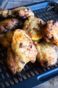 Tuscan Chicken Thighs just out of the air fryers, piled up on the air fryer tray.