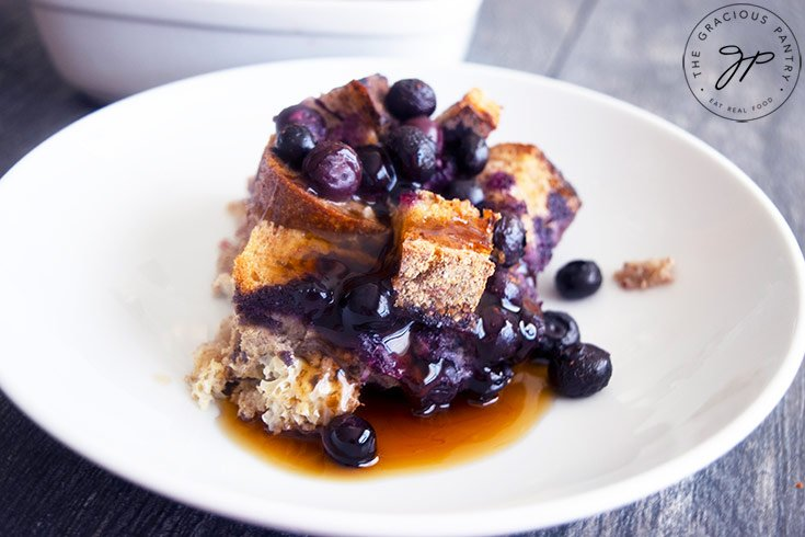 The finished Blueberry French Toast Casserole and a portion served on a plate.