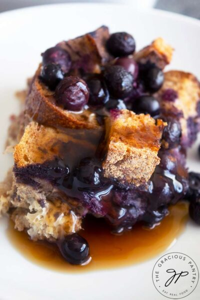 A single serving of Blueberry French Toast Casserole served with maple syrup over the top.