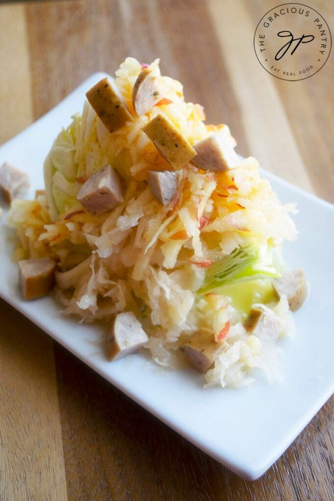 A German wedge salad topped with sauerkraut, shredded apple, chopped sausage and dressing.