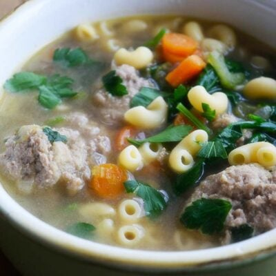 A side view of this Healthy Italian Wedding Soup in a green crock.