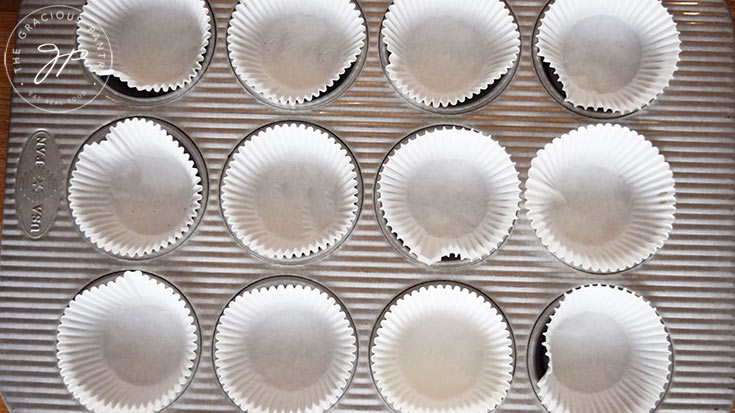 A metal muffin pan, lined with cupcake papers.