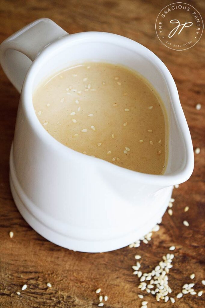 A white, small pitcher filled with this Sesame Vinaigrette.