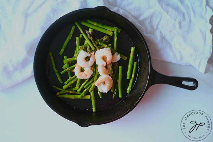Sautéing the shrimp and asparagus in a cast iron pan.