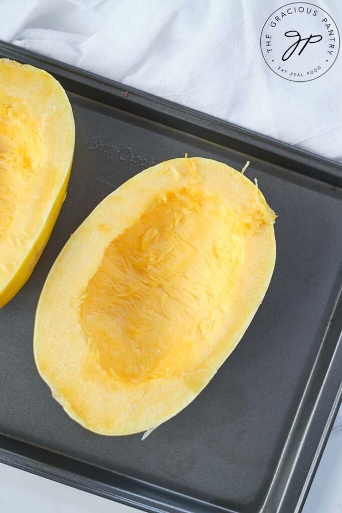 Raw, cut spaghetti squash, cut in half and placed on a baking pan for baking.