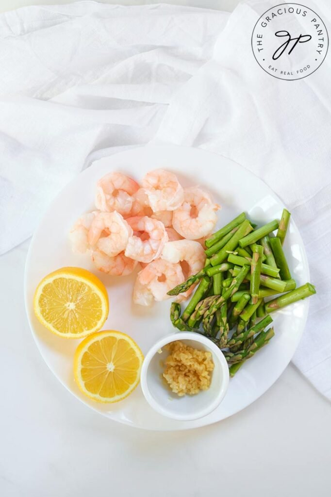 The rest of the recipe ingredients, sitting on a plate, waiting to be used in this Shrimp And Asparagus Spaghetti Squash Spaghetti Recipe. Shrimp, fresh lemon, minced garlic and cut asparagus.