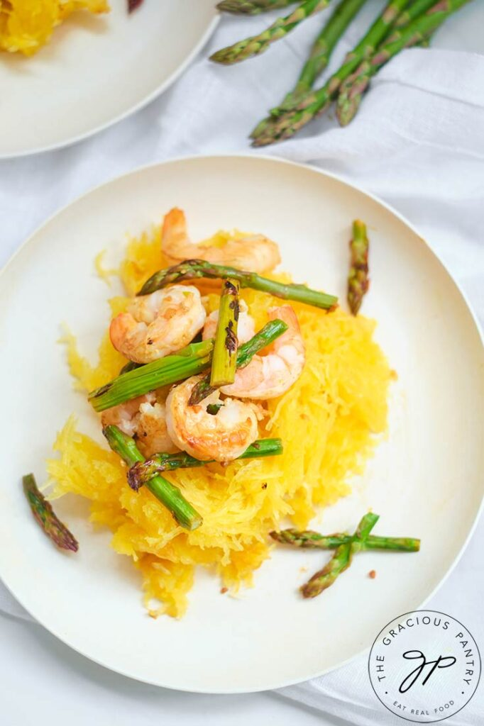 A single white, round plate set with this Shrimp And Asparagus Spaghetti Squash Spaghetti, ready to eat.