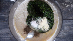 Adding the spinach and spices to the food processor for this Healthy Spinach Artichoke Dip Recipe