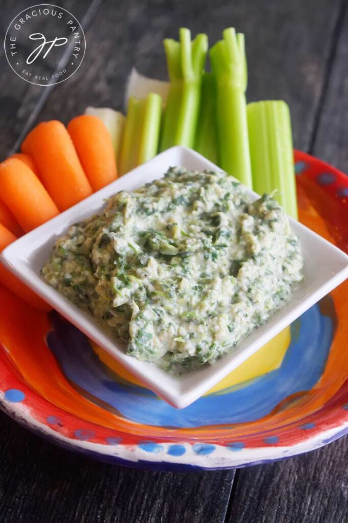 A side view of the served Healthy Spinach Artichoke Dip with carrots and celery sticks sitting just behind it.