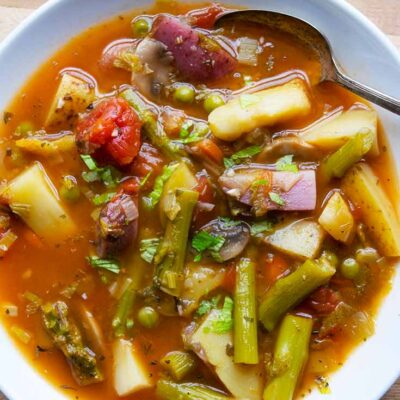 An overhead view looking down into a white bowl filled with this Spring Minestrone Soup Recipe